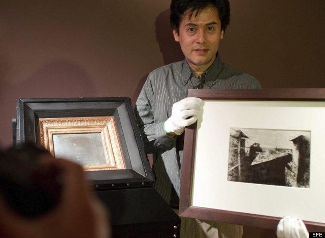 """MHM002 MANNHEIM (ALEMANIA) 30/07/2012.- El restaurador Claude Wang Sui posa con la fotografía más antigua existente (i) y una reproducción de la misma en el museo Reiss Engelhorn en Mannheim, Alemania, hoy, lunes 30 de julio de 2012. La fotografía de 1826, titulada """"Vista desde la ventana en Le Gras"""", del pionero fotógrafo francés Nicephore Niepce será parte de la exhibición """"El nacimiento de la fotografía"""", que comenzará el 9 de Septiembre de 2012. EFE/Uwe Anspach"""